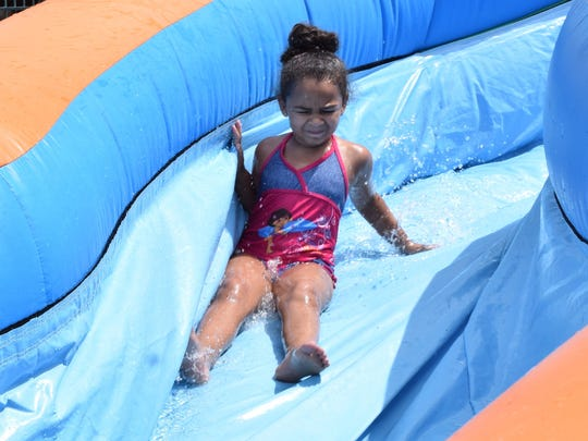 Charli Jones, 5, is sprayed by water as she slides