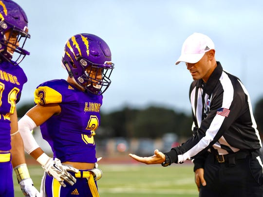 Ozona's Alec Lara double-checks the coin following the toss at midfield Friday, Sept. 29, 2017, before the Lions' home game against Reagan County.