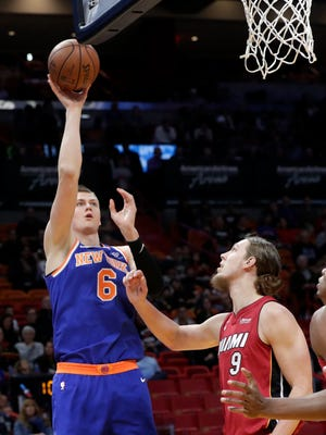 New York Knicks' Kristaps Porzingis (6) shoots over Miami Heat's Kelly Olynyk (9) during the first half of an NBA basketball game, Friday, Jan. 5, 2018, in Miami.