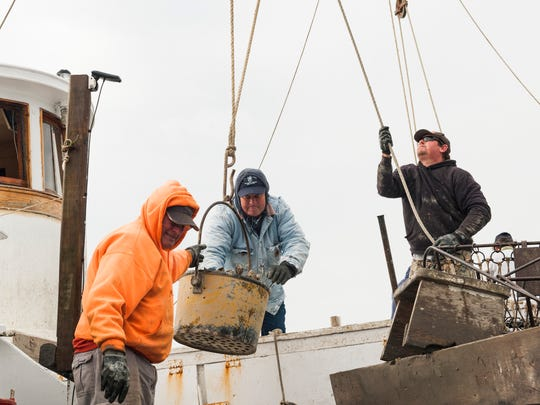 Ed Charnock, left, and Jason Charnock, right, unload