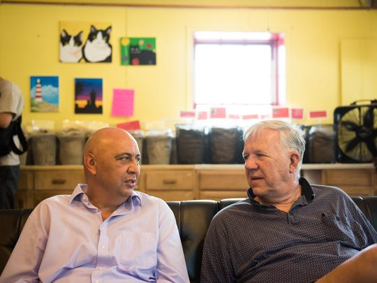 Zijad Rucic, left, a native Bosnian who moved to the United States in 2001, speaks with Bill Ritter, of Hanover, right, while Rucic was attending his daughter's book signing Saturday July 23, 2016 at Merlin's Coffee in Hanover.