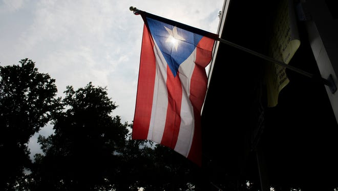 A Puerto Rican flag hangs above a stage during a Puerto Rican festival Thursday, July 27, 2017 in Vineland.
