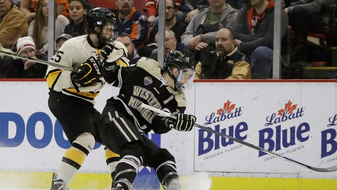 Michigan Tech forward Mike Neville, left, and Western Michigan forward Griffen Molino chase the puck during the first period of the Great Lakes Invitational final at Joe Louis Arena on Dec. 30, 2016.
