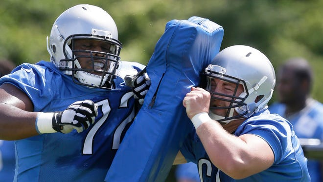 Detroit Lions center Taylor Boggs, right, runs a drill with guard Laken Tomlinson during minicamp June 16, 2015, in Allen Park.