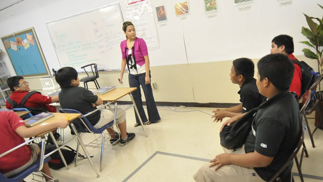 Seventh-grade teacher Jannale Aflague, standing, talks to students in her reading class at Agueda Johnston Middle School in August 2010.