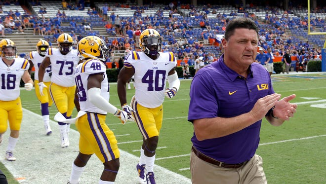LSU head coach Ed Orgeron takes the field with players during warm ups before the first half of an NCAA college football game against Florida, Saturday, Oct. 7, 2017, in Gainesville, Fla.