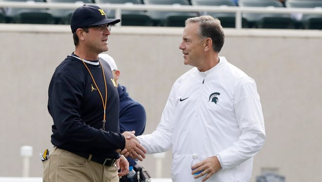 Michigan head coach Jim Harbaugh, left, greets Michigan State head coach Mark Dantonio at midfield before their college football game, Saturday, Oct. 29, 2016, in East Lansing.
