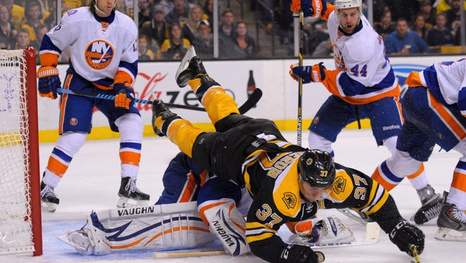 Boston Bruins center Patrice Bergeron (37) falls on top of New York Islanders goalie Chad Johnson (30) during the first period Oct. 23 at TD Banknorth Garden.