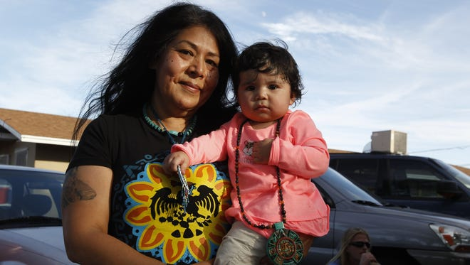 Quetzalli Torres holds her granddaughter Luna in her arms during the first celebration of Indigenous Peoples Day in Phoenix  on Oct. 10, 2016.