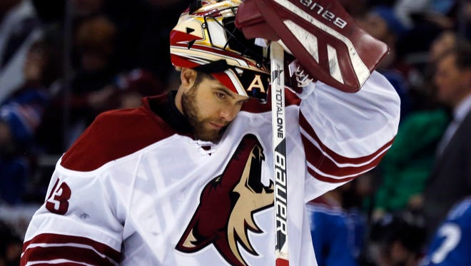 Arizona Coyotes goalie Mike McKenna reacts after giving up a goal to the Colorado Avalanche in the second period of an NHL hockey game Monday, Feb. 16, 2015, in Denver.