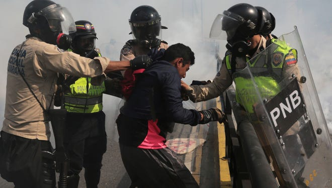 Venezuelan state security forces detain a protester amid tear gas during a demonstration by opponents of President Nicolas Maduro blocking a major highway in Caracas, Venezuela, May 20, 2017.