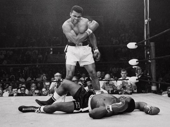 FILE -- Heavyweight champion Muhammad Ali, then known as Cassius Clay, stands over challenger Sonny Liston, shouting and gesturing shortly after dropping Liston with a short hard right to the jaw, May 25, 1965 in Lewiston, Me.