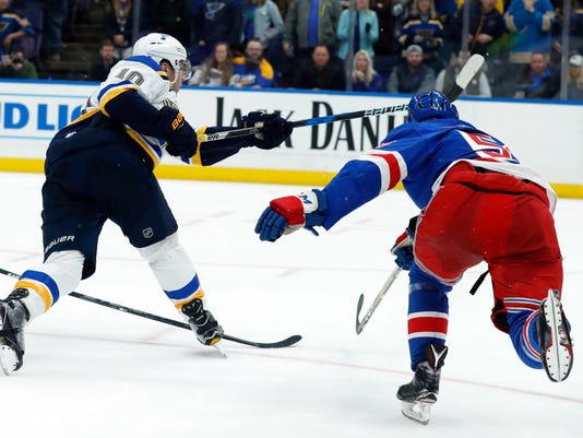St. Louis Blues' Brayden Schenn, left, scores the game-winning goal past New York Rangers' John Gilmour, right, during overtime in an NHL hockey game Saturday, March 17, 2018, in St. Louis. The Blues won 4-3. (AP Photo/Jeff Roberson)