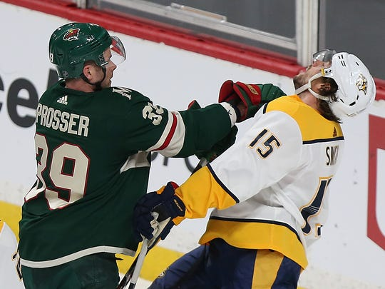 Minnesota Wild's Nate Prosser (39) shoves Nashville Predators' Craig Smith (15) in the first period of an NHL hockey game Saturday, March 24, 2018, in St. Paul, Minn. (AP Photo/Stacy Bengs)