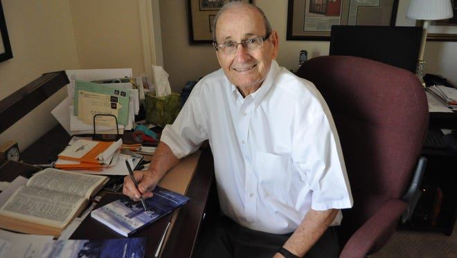 """Henry Blount sits in his office with a copy of his latest book """"Living Faithfully in The Age of Terror."""""""