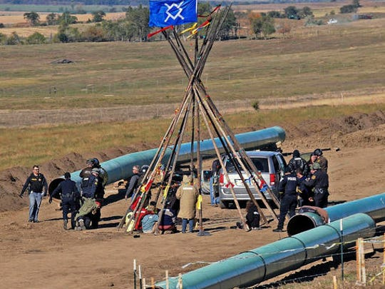 FILE- In this Oct. 10, 2016, file photo, Law enforcement officers, left, drag a person from a protest against the Dakota Access Pipeline, near the town of St. Anthony in rural Morton County, N.D. North Dakota Sen. John Hoeven said Tuesday, Jan. 31, 2017, that the Acting Secretary of the Army has directed the Army Corps of Engineers to proceed with an easement necessary to complete the Dakota Access pipeline.