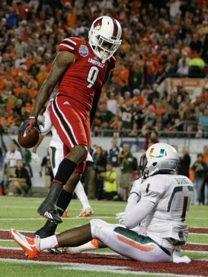 Louisville's Devante Parker stands over Miami's Artie Burns after scoring the Cards' first touchdown during the Dec. 28 Russell Athletic Bowl in Orlando.
