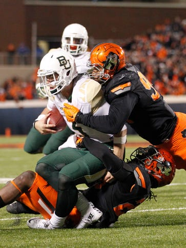 Baylor quarterback Jarrett Stidham is tackled by two