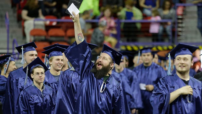 Northeast Wisconsin Technical College graduates wave to family members as they enter the Resch Center in Ashwaubenon on May 16.