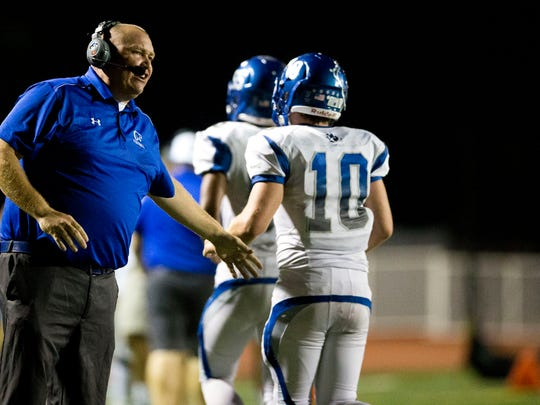 Barron Collier Head Coach Mark Jackson congratulates his team after the defense blocked a Naples extra point kick in the first half of action at Naples High School Friday, October 28, 2016 in Naples. Naples led 28-7 over Barron Collier at the half.