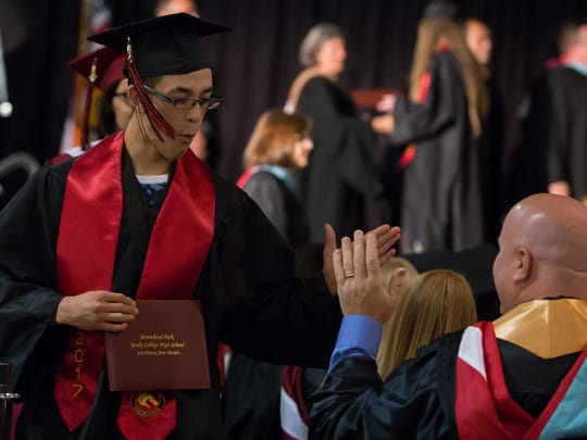 Marcos Holguin high-fives faculty member Mike Kingery during the 2017 Arrowhead Park Early College High School graduation held at the Las Cruces Convention Center on May 19, 2017.