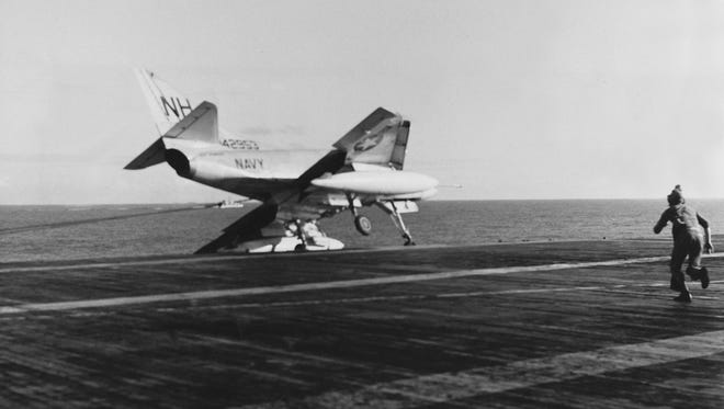 An A4D Skyhawk teeters on the very edge of the flight deck after busting a wheel. The man running in jumped up and hung from the wingtip, precariously balancing the plane for a few precious moments until a dozen others took his lead and balanced the plane until a crane could be attached. The runner saved the airplane, and probably the pilot's life.