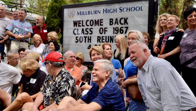 The Class of '67 poses in front of sign on the front lawn of Millburn High School.