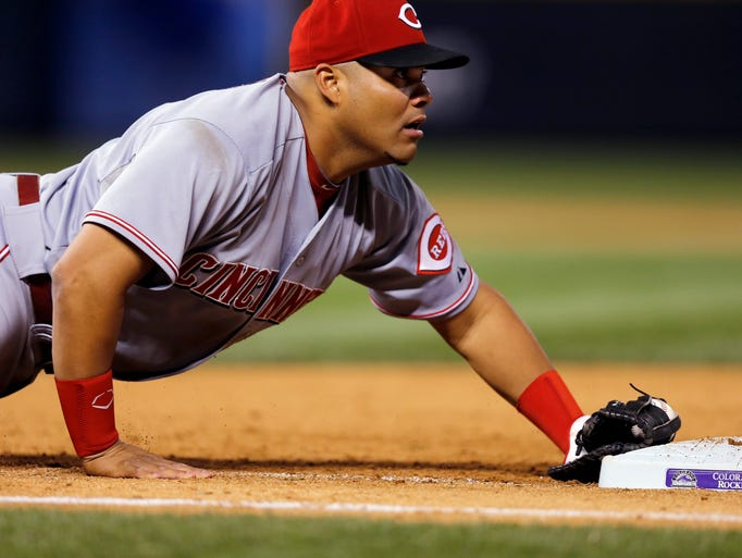Cincinnati Reds first baseman  Brayan Pena dives back to tag first base to complete a double play and end the baseball game against the Colorado Rockies.
