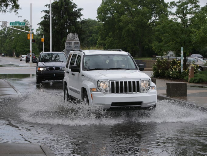 Drivers splash through deep puddles off College Ave. in Broad Ripple village, after a morning of heavy rain on Wednesday, June 4th, 2014.