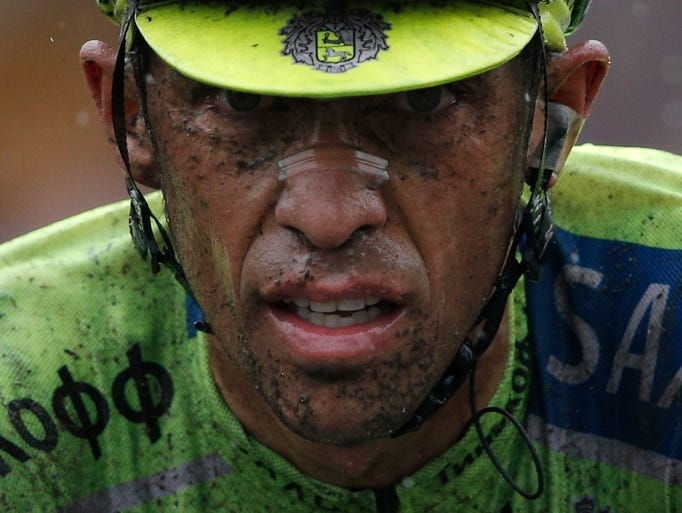 Spain's Alberto Contador crosses the finish line with a delay of more than two minutes on his main rivals during the fifth stage of the Tour de France cycling race over 155 kilometers (96.3 miles) with start in Ypres, Belgium, and finish in Arenberg, France, Wednesday, July 9, 2014. (AP Photo/Peter Dejong)