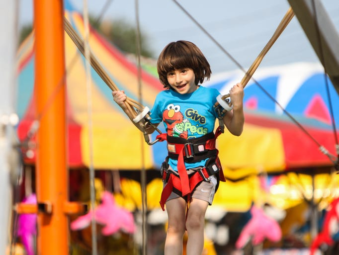 East Brunswick, NJ - A child on a bouncing trampoline ride at the Middlesex County Fair.