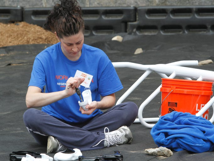 Suzanne Del Pozzo from Regeneron pharmaceuticals, helps assembles a playground at the Carl L. Dixson Primary School in Elmsford on June 25, 2014.  Regeneron along with volunteers from the community, volunteered their time to help build the playground.