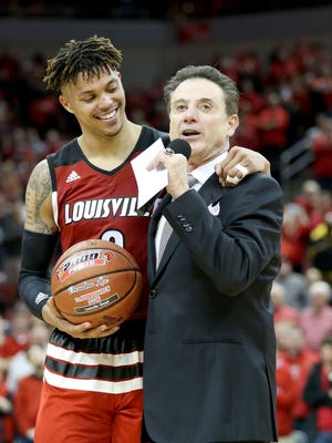 Damion Lee of the Louisville Cardinals hugs head coach Rick Pitino as he talks to the crowd following the 56-53 win over the Georgia Tech Yellow Jackets.