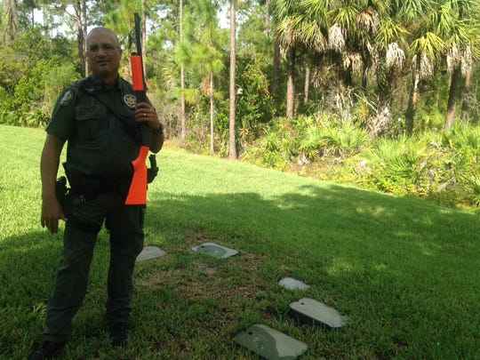 FWC officer Felix Collazo searches for a bear in the Bella Terra community. He's toting a shotgun with beanbag shells.