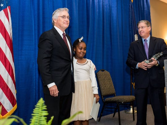 In 2017 Dr. Kip Schumacher hugs Zhorie'l Tapo, a Plantation Elementary student in The Leader in Me, as board member Rob Eddy looks on. She has been named a Scholastic Kid Reporter for 2019-2020.
