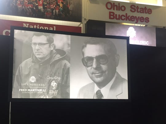 """Images of Ashland University's Hall of Fame coach Fred Martinelli appear on a big screen inside the Woody Hayes Athletic Center as he is honored by Ohio State as one of """"Ohio's Finest."""""""