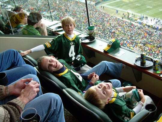 JK Scott (top) attends a Packers-Jets game in December 2006 with his sister Christi (middle) and brother Charlie (right) at Lambeau Field.