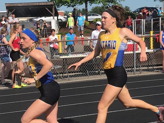 Ontario's  Grace Maurer takes the baton from Anna Gregg on their regional runner-up 4x800 relay.