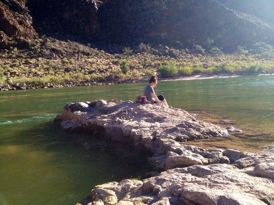 Megan Finnerty relaxes by the Colorado River at the bottom of the Canyon after hiking the Bright Angel Trail.