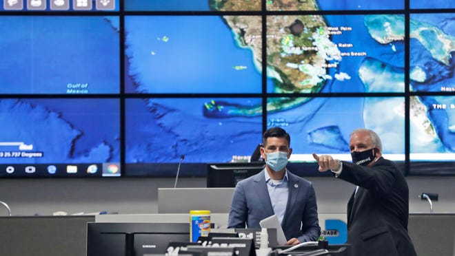 Miami-Dade County Mayor Carlos Gimenez, right, gives a tour to Acting Secretary of Homeland Security, Chad Wolf, of the Miami-Dade Emergency Operations Center, Monday, June 8, 2020, in Doral, Fla. Wolf, who also toured the National Hurricane Center, spoke during a news conference on the on DHS's operational readiness for the hurricane season.