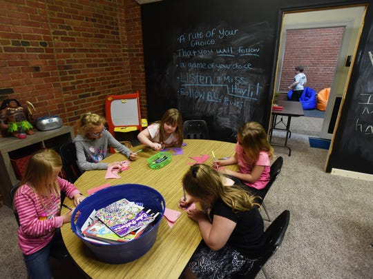 A group of school-age girls do crafts at the Little Barnyard Childcare Center in Zanesville recently.