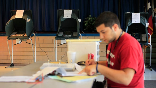 Michael Zamora/Caller-TimesVoting booths sit empty Tuesday, Nov. 8, 2011 inside the Wilson Elementary gym as Latchkey Coach Sergio Santoyo does paperwork nearby.