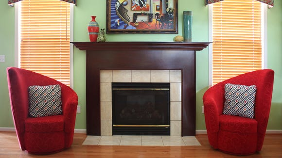 A pair of asymmetrical chairs flank the fireplace in this playful design.