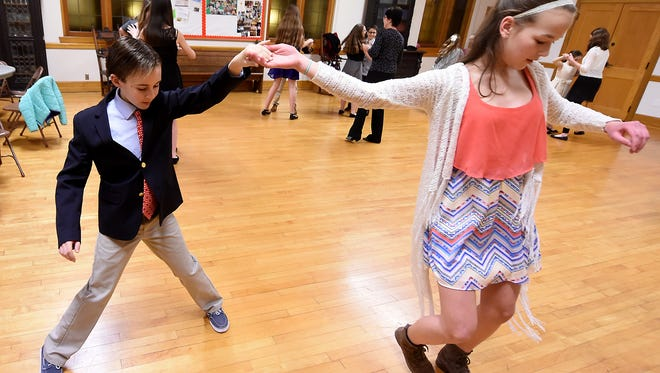 Alex Gleba, 13, spins out 13-year-old Olivia Sharp while the duo go over swing steps during ballroom dance class at St. John the Baptist Episcopal Church.  Over 20 kids from ages 9 through 14 take the six-week class where they learn fox trot, waltz, rumba and swing.