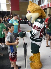Wild mascot Nordy signs a fan's cap Thursday during
