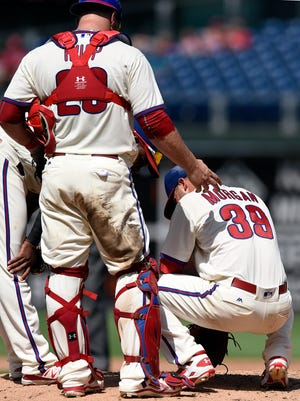 Philadelphia Phillies catcher Cameron Rupp checks on starting pitcher Adam Morgan who was hit by a line drive by Colorado Rockies' Nick Hundley in the fourth inning Sunday. Morgan exited the game with a left forearm contusion. X-rays were negative.