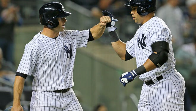 The Yankees' Carlos Beltran, right, is greeted by teammate Brett Gardner after hitting a two-run home run against the Boston Red Sox during the third inning at Yankee Stadium.