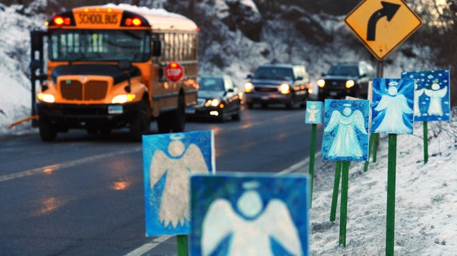A bus traveling from Newtown, Conn., to Monroe stops near 26 angel signs posted along the roadside in Monroe, Conn., on Jan. 3, 2013, the day classes for Sandy Hook Elementary School students resumed after the Dec. 14, 2012 shooting.
