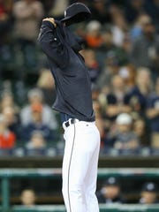 Tigers manager Brad Ausmus removes his sweatshirt after