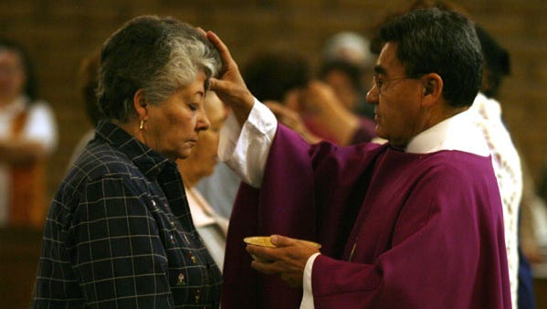 The Rev. Raul Trigueros of Christ the King Catholic Church applies ashes to the forehead of Petra Hernandez during an Ash Wednesday Mass in 2016.